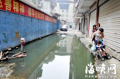 道路被水淹没,居民贴墙角走