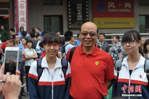 北京市陈经纶中学考点外,一名老师与即将参加考试的一对双胞胎女孩合影。 中新网记者 李泊静 摄