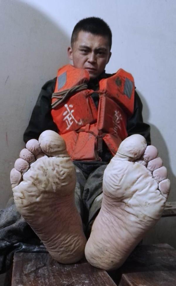 7月3日,武警安徽总队第一支队战士焦磊在两条板凳上小憩,他的双脚已经在洪水里连续浸泡了19个小时。 新华社发