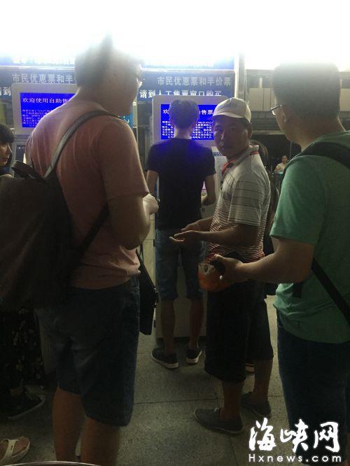 黄牛(戴帽者)来到轮渡码头自动售票机前,向记者索要身份证,并谎称自己有﹃内部卡﹄,可买上岛船票