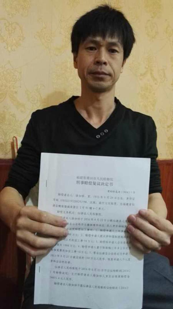 徐加珍手持莆田市检察院作出的刑事赔偿复议决定书。