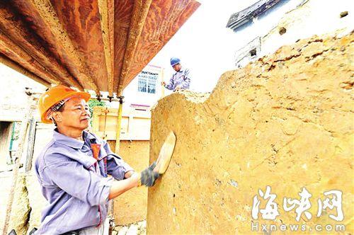 土墙夯实后,工人用樟木板不断拍打