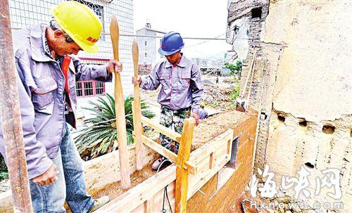 工人在墙两侧搭上木板,装土之后,用木棍将土夯实