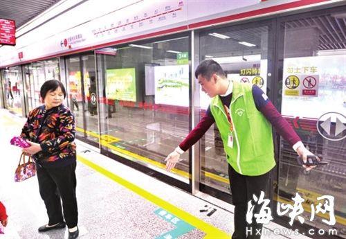 志愿者提醒乘客,不要越过黄线候车