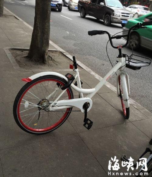 市区公共人行道上,一辆hellbike单车的座包被卸,孤零零地放在人行道上。