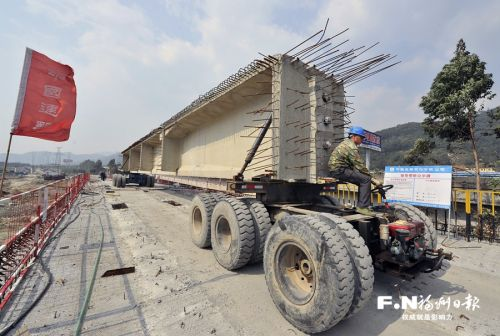 在山兜高架桥施工现场,专用工程车正运送预制梁。