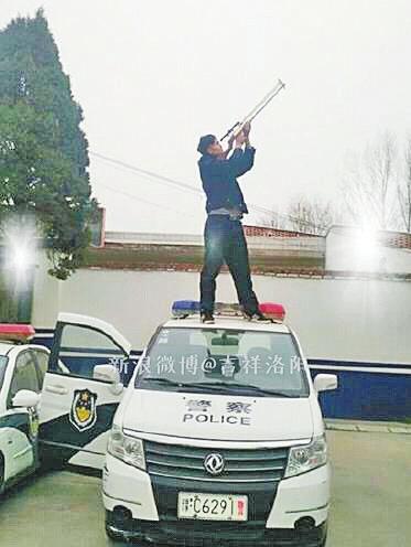 男子疑似持枪站警车顶玩自拍 当地警方已介入调查