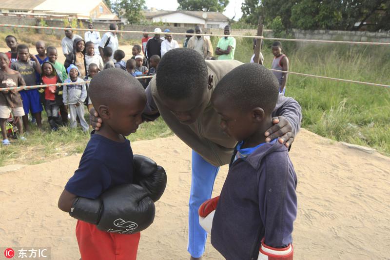 近日,津巴布韦奇通圭扎,在一个拳击台上,一名裁判运在比赛开始之前给两名儿童选手做指导。Tsvangirayi Mukwazhi/东方IC
