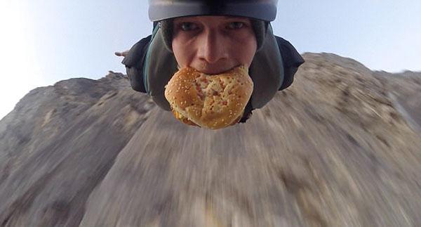 瑞士小伙偏爱另类跳伞 嘴里夹汉堡从山崖跃下