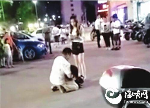 持刀男挟持一女子,蹲在地上,与旁边女子争执