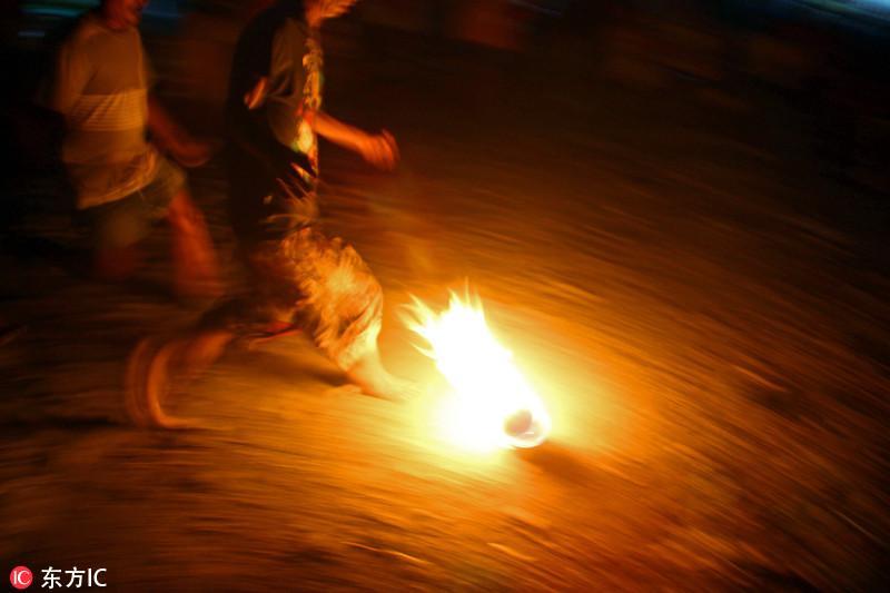 踢球也有新创意?印尼踢火球比赛参赛者赤脚踢球