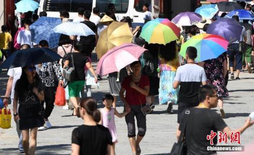 7月12日,厦门一景点游客们纷纷打起伞遮挡烈日。张斌 摄