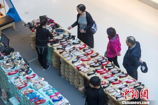 资料图:山西太原,民众正在商场选购鞋子。 张云 摄