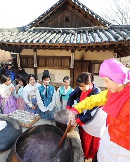 韩国庆冬至提前:民俗村熬红豆粥 美女游客排队领