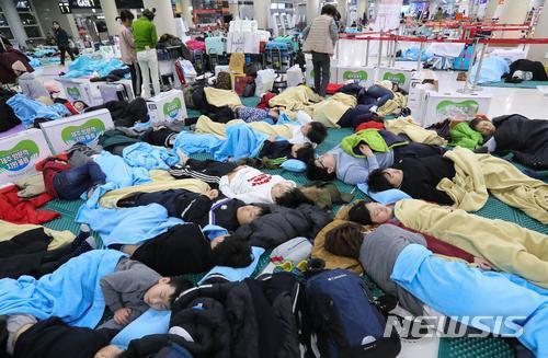 韩国济州遭暴雪袭击 2500名滞留游客被迫机场打地铺