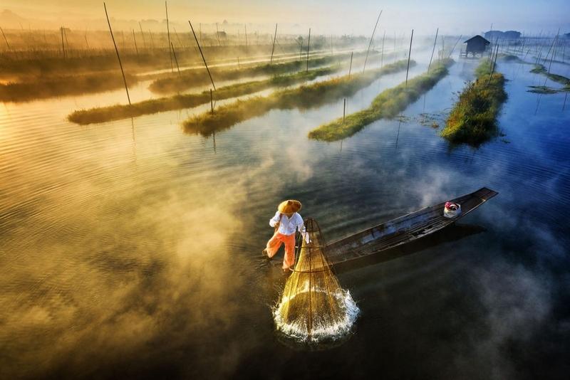 佐伊•亚尔(Zay Yar)获奖作品:缅甸渔夫在朝阳下边用脚划船边用渔具捕鱼。