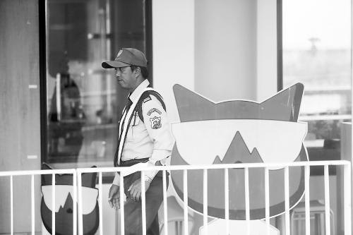 图说:    10日,一名泰国保安把守着懒猫旅游公司位于普吉岛的游客接待中心。 崔 萌 摄