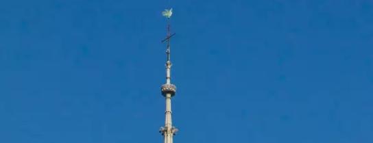 火灾前,巴黎圣母院顶上的箭形塔尖和高居其上的公鸡风向标(图源:法媒)
