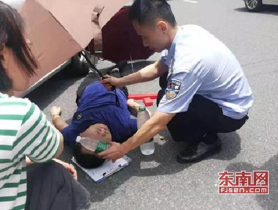 莆田:男子晕倒在地 路过交警撑伞遮阴