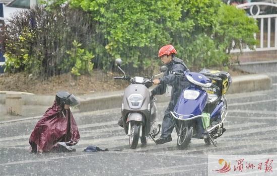 女子雨天骑车摔倒 外卖小哥上前援助