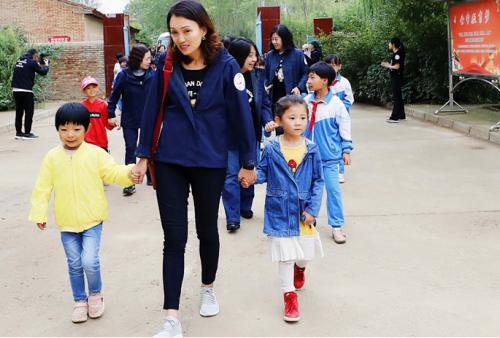 百胜中国CEO屈翠容(Joey Wat)牵着下中滩小学的孩子一起走进校园