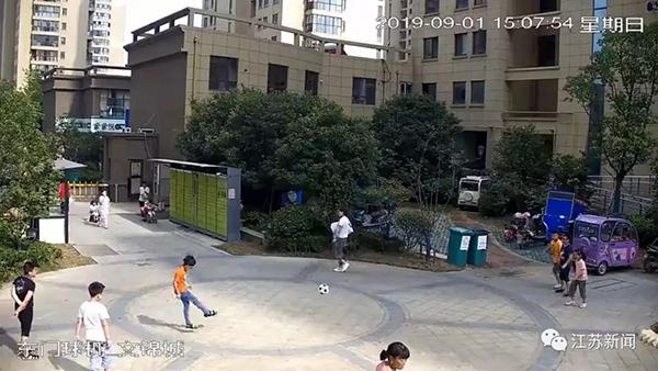 男孩踢球砸中过路女子 同行男子竟一觉将其踹飞