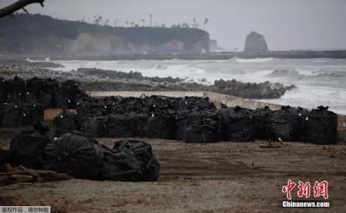 资料图:日本福岛第一核电站核灾难清理的被污染的土壤、叶子和垃圾被放入大黑塑料袋中弃置在海边。