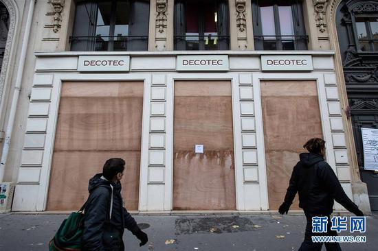 12月5日,在法国巴黎,行人从一家受罢工影响关闭的商店前走过。 新华社发(奥雷利安·莫里萨尔摄)
