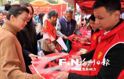 志愿者向到场市民送春联。记者 郑帅 摄
