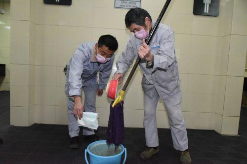 保洁人员在自来水里添加消毒粉,进行卫生保洁消杀。
