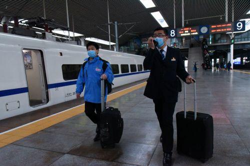 福州站客运车间主任朱剑峰推着箱包,一路护送支援武汉抗疫的陈建华进站乘车。拍摄:江曲