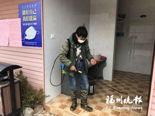 林立俤在对村里的公厕进行消杀作业 。