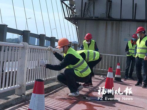 市政施工人员对淮安大桥防护栏进行涂装。