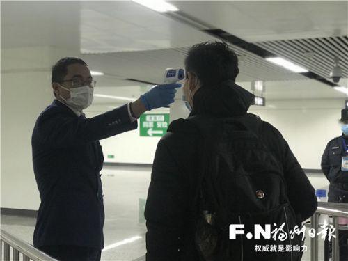 地铁福州火车南站站的站区长粟建华为乘客测量体温。记者 林文婧 摄