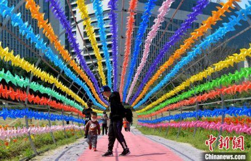 图为戴着口罩的民众在福州花海公园游玩。 张斌 摄