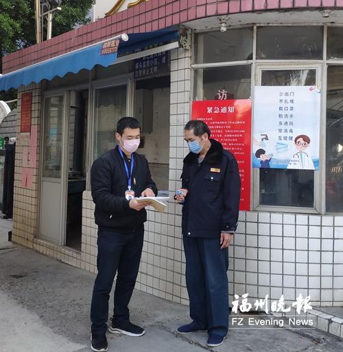 赵铭飞(左)走访小区,检查物业部门防疫工作台账。