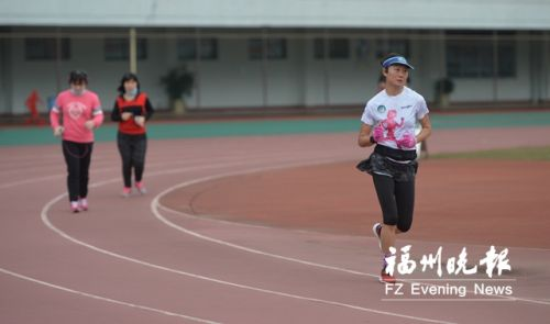 马拉松爱好者何小姐(右)在省体田径场跑步。
