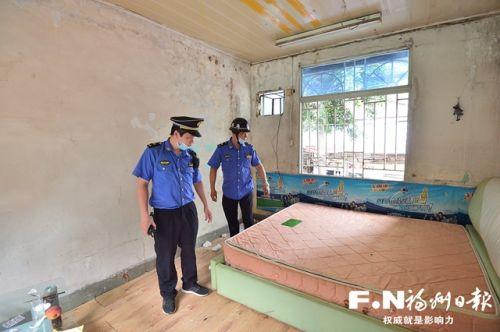 拆除危房前,城管队员进入室内进行最后一次检查。 记者 邹家骅 摄